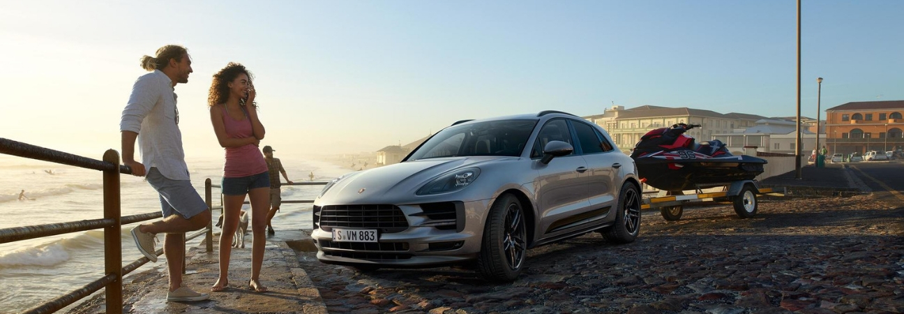 2019 Porsche Macan parked beachside with a jet ski in tow